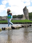 SX05751 Laura crossing stepping stones at Ogmore Castle.jpg